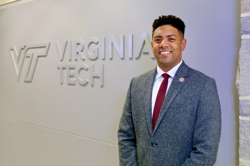 Kory Trott in front of a wall with the Virginia Tech logo.